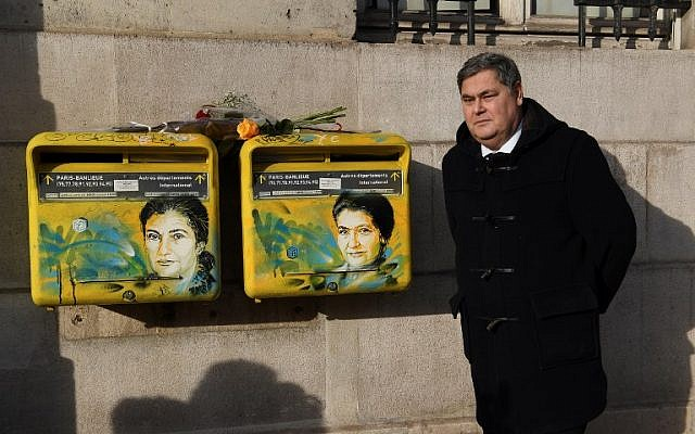 French lawyer Pierre-Francois Veil poses next to recently vandalized letter boxes displaying a portrait of his mother, late French politician and Holocaust survivor Simone Veil, on February 11, 2019 in the 13th arrondissement of Paris. (Christophe Archambault/AFP)