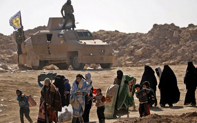 Civilians fleeing the battered Islamic State-held holdout of Baghouz in the eastern Syrian province of Deir Ezzor walk past an armored vehicle and into a nearby area held by the Syrian Democratic Forces (SDF) on February 12, 2019. Delil souleiman/AFP)