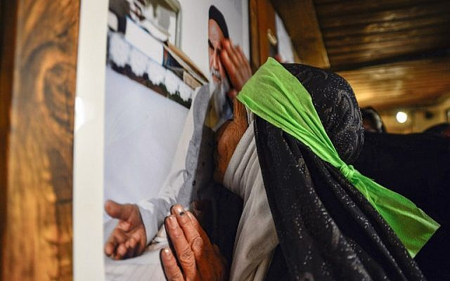 An Iranian woman kisses a portrait of Islamic Revolution leader Ayatollah Ruhollah Khomeini, as she visits the house where he lived during his 13-year-exile in Iraq, along al-Rasul street near the shrine of Imam Ali in the central holy city of Najaf on February 13, 2019, while marking the 40th anniversary of the Islamic Revolution in Iran. (Haidar HAMDANI / AFP)