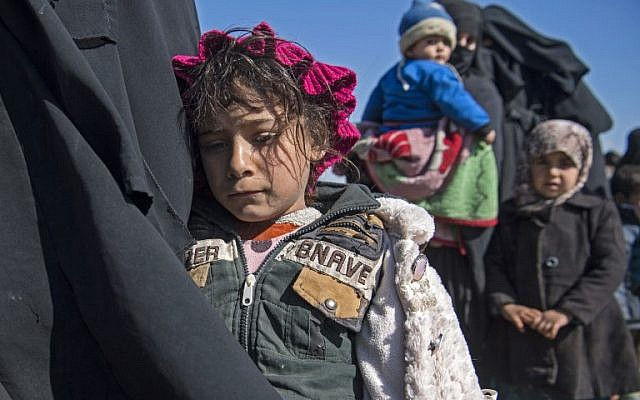 Women and children stand in a field after they fled from the Baghouz area in the eastern Syrian province of Deir Ezzor  during an operation to expel hundreds of Islamic State group jihadists from the region, on February 12, 2019. (Fadel SENNA / AFP)