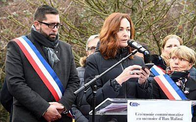 Sainte-Genevieve-des-Bois mayor Frederic Petitta, left, listens to a speech by French writer Emilie Freche, on February 13, 2019 in Sainte-Genevieve-des-Bois, at a ceremony honoring Ilan Halimi, two days after two trees planted in memory of the 23-year-old Jewish man abducted and killed over a decade ago by an anti-Semitic gang were found vandalized. (Bertrand Guay/AFP)