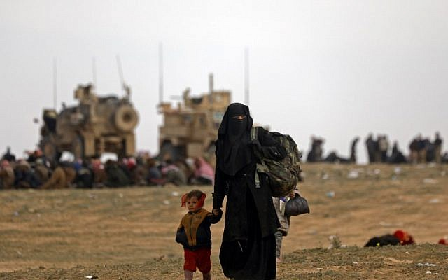Civilians fleeing the Islamic State's group embattled holdout of Baghouz walk in a field on February 13, 2019. (Delil Souleiman/AFP)