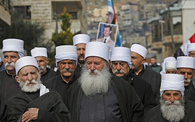Druze residents of the Golan Heights carry a portrait of Syrian President Bashar al-Assad during a rally in the village of Majdal Shams on February 14, 2019 (JALAA MAREY / AFP)