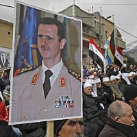 Druze residents of the Golan Heights carry a portrait of Syrian President Bashar al-Assad during a rally in the village of Majdal Shams in the Golan Heights on February 14, 2019 (JALAA MAREY / AFP)