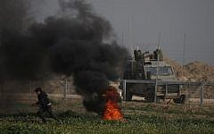 A Palestinian protester runs near burning tires during a demonstration near the fence along the border with Israel, east of Gaza City, on February 15, 2019. An Israeli military vehicle is pictured on the other side of the fence. (Said Khatib/AFP)