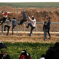 Palestinians climb the security fence along the border between Israel and the Gaza Strip, during clashes east of Gaza City, on February 15, 2019. (Said Khatib/AFP)