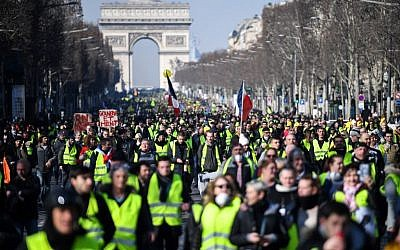 People walk down the Champs Elysees avenue on February 16, 2019 during the 14th consecutive week of 'yellow vest' protests. (Eric Feferberg/AFP)