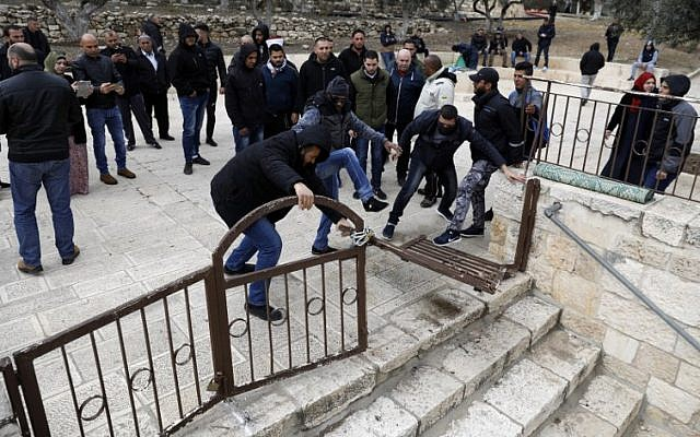 Palestinian demonstrators break open the locked entrance to the Gate of Mercy compound outside the Al Aqsa Mosque on the Temple Mount in Jerusalem's Old City, February 18, 2019. (Ahmad Gharabli/AFP)
