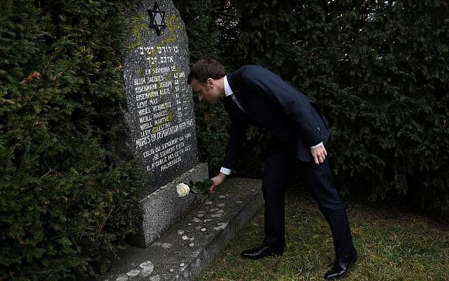 French President Emmanuel Macron lays a white rose on a grave vandalized with swastikas during a visit at the Jewish cemetery in Quatzenheim, on February 19, 2019, on the day of a nationwide marches against a rise in anti-Semitic attacks. (Frederick Florin/ Pool/ AFP)