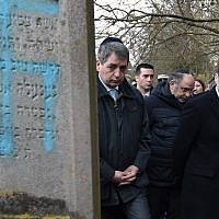 French President Emmanuel Macron looks at a grave vandalized with a swastika during a visit at the Jewish cemetery in Quatzenheim, on February 19, 2019, on the day of nationwide marches against a rise in anti-Semitic attacks. (Photo by Frederick FLORIN / POOL / AFP)