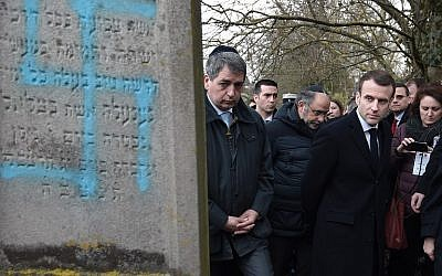 Illustrative: French President Emmanuel Macron looks at a grave vandalized with a swastika during a visit at the Jewish cemetery in Quatzenheim, on February 19, 2019, on the day of nationwide marches against a rise in anti-Semitic attacks. (Frederick Florin/Pool/AFP)