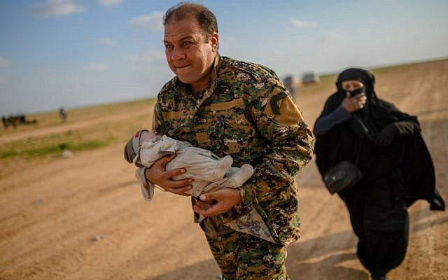 Mostapha Bali, the spokesman for the Kurdish-led Syrian Democratic Forces (SDF), carries a baby followed by a woman after fleeing the Islamic State (IS) group's last holdout of Baghouz, in Syria's northern Deir Ezzor province, on February 22, 2019. (Bulent KILIC / AFP)