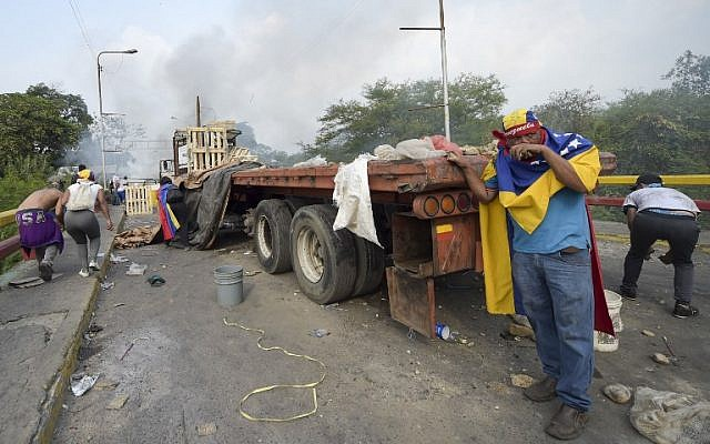 Demonstrators duck behind a truck during clashes with the security forces at the Francisco de Paula Santander international bridge Bridge linking Cucuta, Colombia, and Urena, Venezuela, during an attempt to cross humanitarian aid over the border into Venezuela, on February 23, 2019. (RAUL ARBOLEDA / AFP)