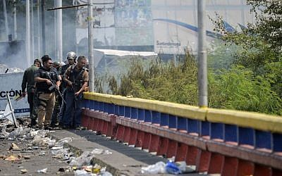Venezuelan Bolivarian National Guard members check damages at the Francisco de Paula Santander international bridge in Urena, Venezuela on February 24, 2019, following protests in the region after Venezuelan President Nicolas Maduro ordered a temporary closure of the border with Colombia to prevent the humanitarian aid from entering the country. (Luis Robayo/AFP)