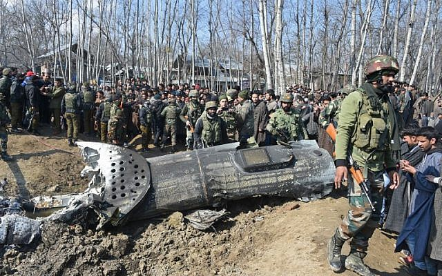 Indian soldiers and Kashmiri onlookers stand near the remains of an Indian Air Force aircraft after it crashed in Budgam district, some 30 kilometers from Srinagar on February 27, 2019. (Tauseef Mustafa/AFP)
