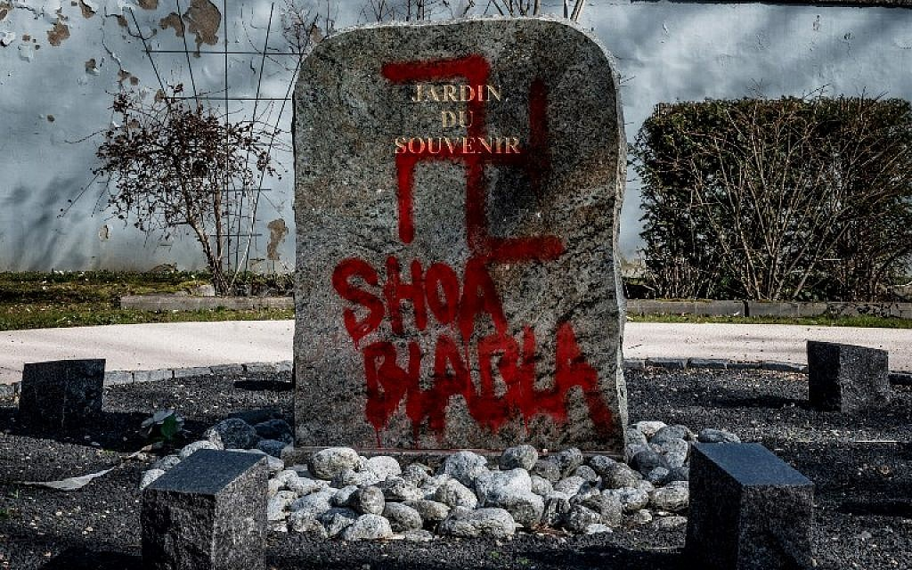 """A swastika and the words """"Shoa blabla"""" on the stele of the """"Jardin du Souvenir"""" (Garden of Memories) after antisemitic graffiti was discovered in the Champagne-au-Mont-d'Or cemetery on February 20, 2019. (JEFF PACHOUD/AFP)"""