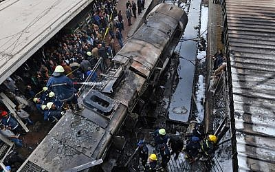 Firefighters and onlookers gather at the scene of a fiery train crash at the Egyptian capital Cairo's main railway station on February 27, 2019. (Stringer/AFP)