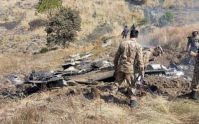 Pakistani soldiers stand next to what Pakistan says is the wreckage of an Indian fighter jet shot down in Pakistan-controlled Kashmir in the Somani area in Bhimbar district near the Line of Control on February 27, 2019. (STR/AFP)
