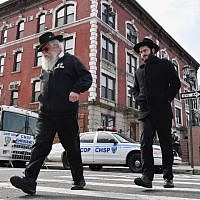Orthodox Jewish men walk past a 'Crown Heights Shmira Patrol' security vehicles in the Brooklyn neighborhood of Crown Heights on February 27, 2019 in New York. (Photo by Angela Weiss / AFP)