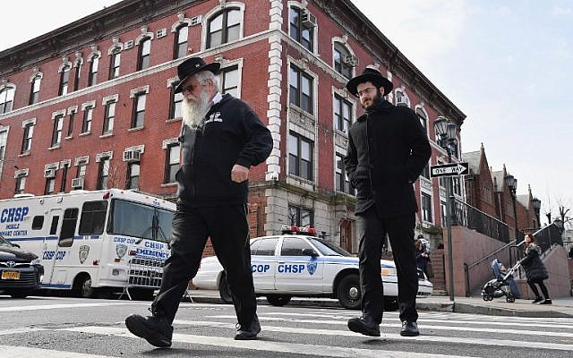Jewish men walk past a 'Crown Heights Shmira Patrol' security vehicles in the Brooklyn neighborhood of Crown Heights on February 27, 2019 in New York. (Angela Weiss/AFP)