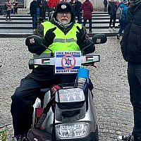 Robert-Willem van Norren promoting a boycott of Israel atop an Israel-made mobility scooter in January 2019. (Michael Jacobs via JTA)