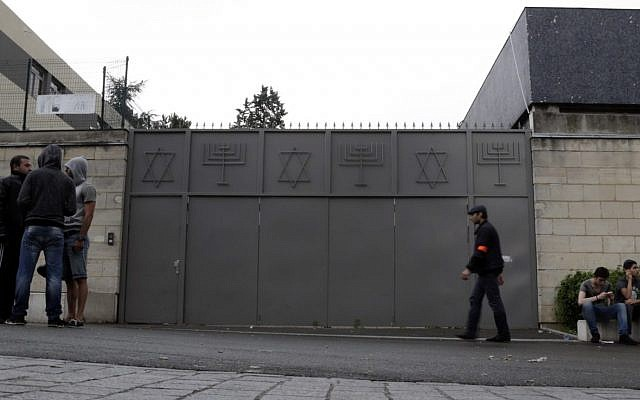 People stand in front of a synagogue with its doors closed in Sarcelles, a suburb north of Paris, on July 20, 2014. (KENZO TRIBOUILLARD/AFP/Getty Images)