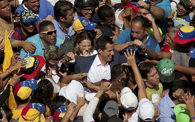 Venezuelan opposition leader Juan Guaido, center, who has declared himself the interim president of Venezuela, greets supporters as he arrives at a demonstration demanding the resignation of President Nicolas Maduro, in Caracas, Venezuela, on February 2, 2019. (AP/Juan Carlos Hernandez)
