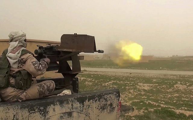 This frame grab from video posted online January 18, 2019, by supporters of the Islamic State group, purports to show a gun-mounted IS vehicle firing at members of the US-backed Syrian Democratic Forces, in the eastern Syrian province of Deir el-Zour, Syria. (Militant Photo via AP)