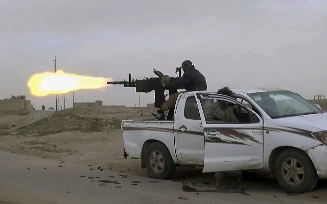 This frame grab from video posted online January 18, 2019, by supporters of the Islamic State group, purports to show a gun-mounted Islamic State group vehicle firing at members of the US-backed Syrian Democratic Forces, in the eastern Syrian province of Deir el-Zour, Syria. (Militant Photo via AP)