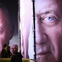 People walk by posters of ex-IDF chief Benny Gantz before the official launch of his election campaign for the April 2019 elections, in Tel Aviv on January 29, 2019. (AP Photo/Oded Balilty)