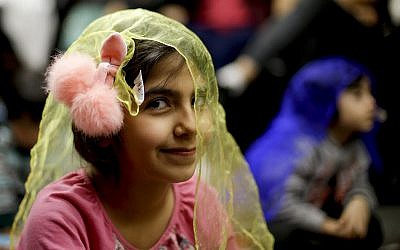 In this Wednesday, January 23, 2019, photo, Melorin Issarezal, 8, plays with a scarf during Persian story time at Irvine public library in Irvine, California. (AP Photo/Chris Carlson)