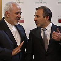 Lebanese Foreign Minister Gebran Bassil, right, speaks with his Iranian counterpart Mohammad Javad Zarif, in Beirut, Lebanon, on February 11, 2019. (AP Photo/Hussein Malla)