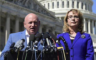 Former Rep. Gabrielle Giffords, D-Ariz., right, listens as her husband Mark Kelly, left, speaks on Capitol Hill in Washington, October 2, 2017. (AP Photo/Susan Walsh, File)