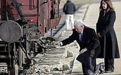 US Vice President Mike Pence kneels beside his wife Karen, right, at a historic freight car during their visit to the former Nazi death camp Auschwitz-Birkenau in Oswiecim, Poland, Friday, Feb. 15, 2019. The freight car was used to transport Jews to the camp. (AP Photo/Michael Sohn)