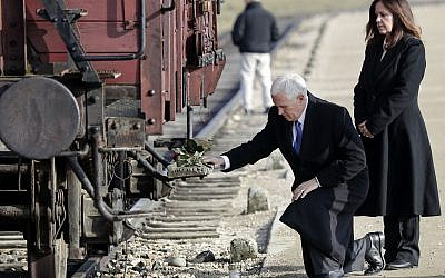 US Vice President Mike Pence kneels beside his wife Karen, right, at a freight car once used to transport Jews, during their visit to the former Nazi death camp Auschwitz-Birkenau in Oswiecim, Poland, Friday, February 15, 2019. (AP Photo/Michael Sohn)
