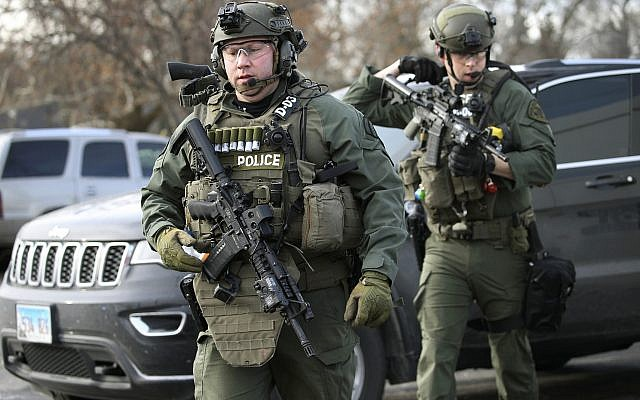 Police officers armed with rifles gather at the scene where an active shooter was reported in Aurora, Illinois on Friday, Feb. 15, 2019. (Antonio Perez/Chicago Tribune via AP)
