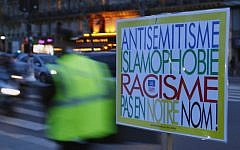 "A poster reading ""Anti-Semitism, Islamophobia, Racism, Not in Our Name"" during a gathering decrying anti-Semitism at Place de la Republique in Paris, February 18, 2019 amid an upsurge in anti-Semitism in France. (AP Photo/Francois Mori)"