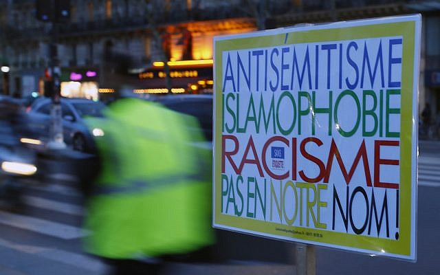 "A poster reading 'Anti-Semitism, Islamophobia, Racism, Not in Our Name"" during a gathering decrying anti-Semitism at Place de la Republique in Paris, February 18, 2019 amid an upsurge in anti-Semitism in France. (AP/Francois Mori)"