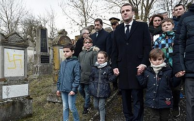 French President Emmanuel Macron holds children by the hands as he visit the vandalized Jewish cemetery in Quatzenheim, eastern France, Tuesday, February 19, 2019. (Frederick Florin, Pool via AP)