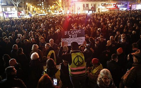 """A man wearing a yellow vest holds a placard reading """"I am jew"""", during a gathering at the Republique square to protest against anti-Semitism, in Paris, France, Tuesday, Feb. 19, 2019.  (AP Photo/Thibault Camus"""