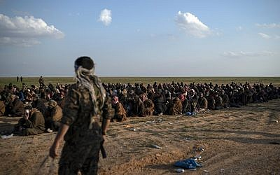 US-backed Syrian Democratic Forces (SDF) fighters stand guard next to men waiting to be screened after being evacuated out of the last territory held by Islamic State militants, near Baghouz, eastern Syria, Friday, Feb. 22, 2019. (AP/Felipe Dana)