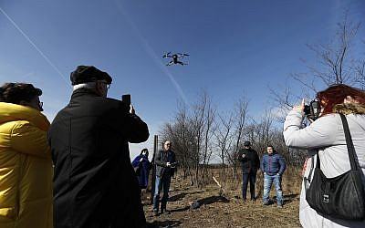 Participants of a conference organized by the Germany-based foundation European Jewish Cemeteries Initiative (EJCI) watch a drone take off over a Jewish cemetery near the village of Reca, Slovakia, February 26, 2019. (Petr David Josek/AP)
