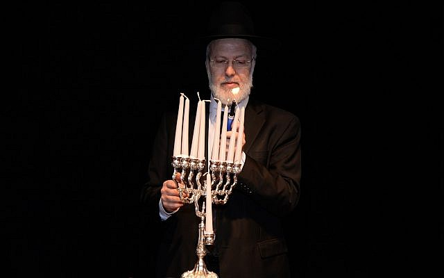In this photo from December 5, 2018, distributed by AMIA, Argentina's Chief Rabbi Gabriel Davidovich holds a menorah at the AMIA Jewish community center in Buenos Aires. (AMIA Jewish community center via AP)