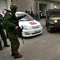 Soldiers stand near a car used by members of the TIPH, Temporary International Presence in Hebron on Wednesday, Feb. 8, 2006. (AP Photo/Emilio Morenatti)