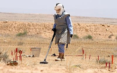 File: A Jordanian deminer uses a detector to clear a minefield in the northern Jordanian- Syrian border area, near Ramtha city, June 28, 2011 (AP Photo/Nader Daoud)