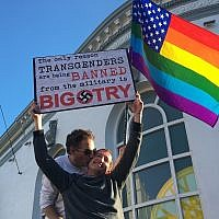 Nick Rondoletto, left, and Doug Thorogood, a couple from San Francisco, wave a rainbow flag and hold a sign against a ban of transgendered people in the military at a protest in the Castro District on July 26, 2017, in San Francisco. (AP Photo/Olga R. Rodriguez)