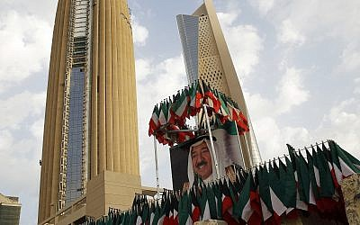 Illustrative: A picture of Kuwait's ruling emir, Sheikh Sabah Al Ahmad Al Sabah, is displayed with surrounding Kuwaiti flags in Kuwait City, on February 14, 2018. (AP Photo/Jon Gambrell)
