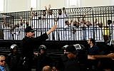 Illustrative: Supporters of the Muslim Brotherhood and other Islamists gesture from the defendants cage as they receive sentences in a mass trial in Alexandria, Egypt, May 19, 2014.   (AP Photo/Heba Khamis)