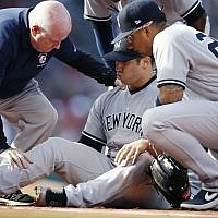A trainer attends to New York Yankees' Luis Cessa, center, after he was injured on a play at first base during the first inning of a baseball game against the Boston Red Sox in Boston, Sunday, Sept. 30, 2018. (AP Photo/Michael Dwyer)