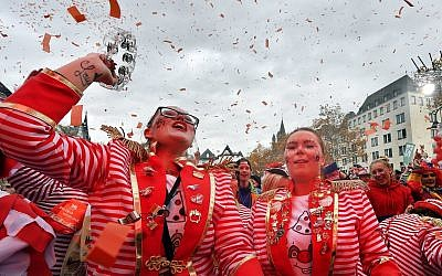Revellers in a red spotlight celebrate the start of the carnival season in the streets of Cologne, Germany, Nov. 11, 2018. (AP Photo/Martin Meissner)